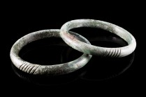 Bronze Age, Pair of Bronze Penannular Bracelets, c. 9th-6th century BC (7.6cm), with vertical bands decoration. Green patina, intact.