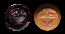 A late roman garnet intaglio. Two birds on a fountain. 