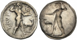 Bruttium, Nomos, Kaulonia, c. 525-500 BC AR (g 8,01 mm 29 h 12) KAVΛ, Apollo standing r., branch in r. hand and l. extended. Above small figure, at r....