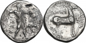 Greek Italy. Bruttium, Kaulonia. AR Stater, c. 475-425 BC. Obv. KAVΛ. Apollo advancing right holding branch, small daimon running on his left arm; to ...