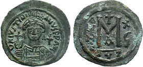 BYZANTINE.Justinian I, AE Follis. Cyzicus. 527-565 AD. DN IVSTINIANVS PP AVG, helmeted, cuirassed bust facing, holding cross on globe and shield with ...