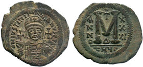 BYZANTINE.Justinian I, AE Follis. Antioch. DN IVSTINIANVS PP AVG, helmeted and cuirassed bust facing, holding cross on globe and shield with horseman ...